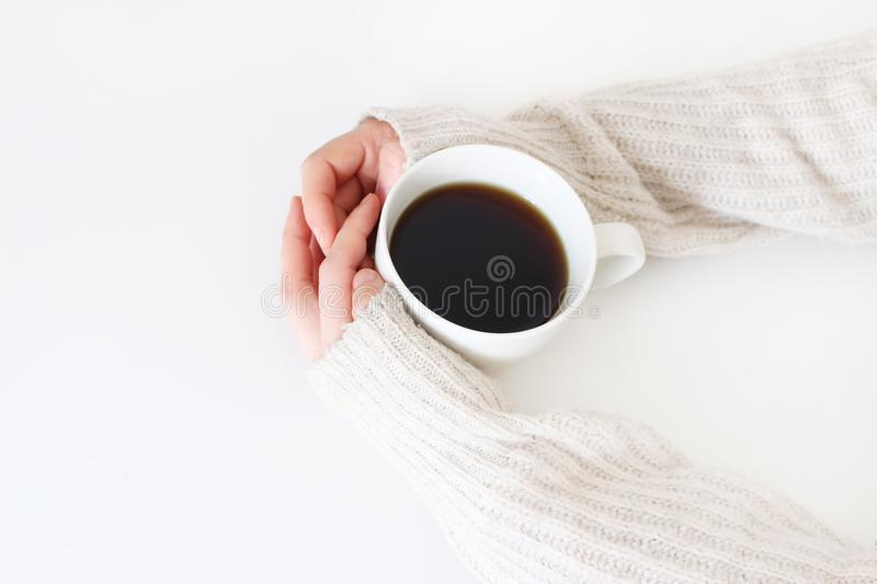 Woman`s hands in sweater holding cup of coffee on white table. Top view, styled stock image. Break, breakfast concept. Woman`s hands in sweater holding cup of stock photography