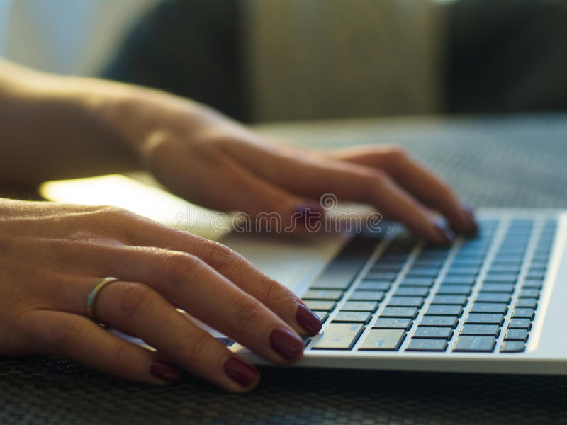 Woman`s hands typing on laptop keyboard in interior, side view of businessman using computer in cafe royalty free stock photo