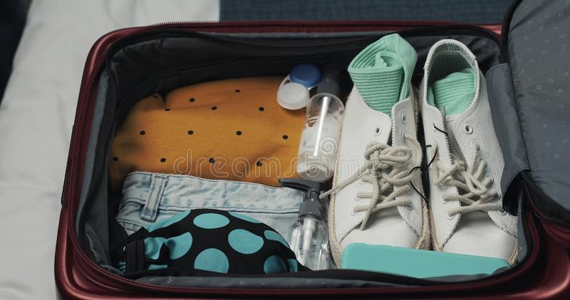 Woman`s hands unpacking suitcase for a journey on the bed at home. Travel preparations. stock photo