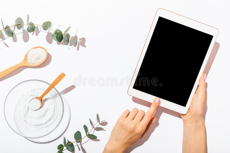 Woman's hands using blank-screen tablet device. Next to homemade organic cosmetics clay mask on white table among eucalyptus twigs, top view stock photos