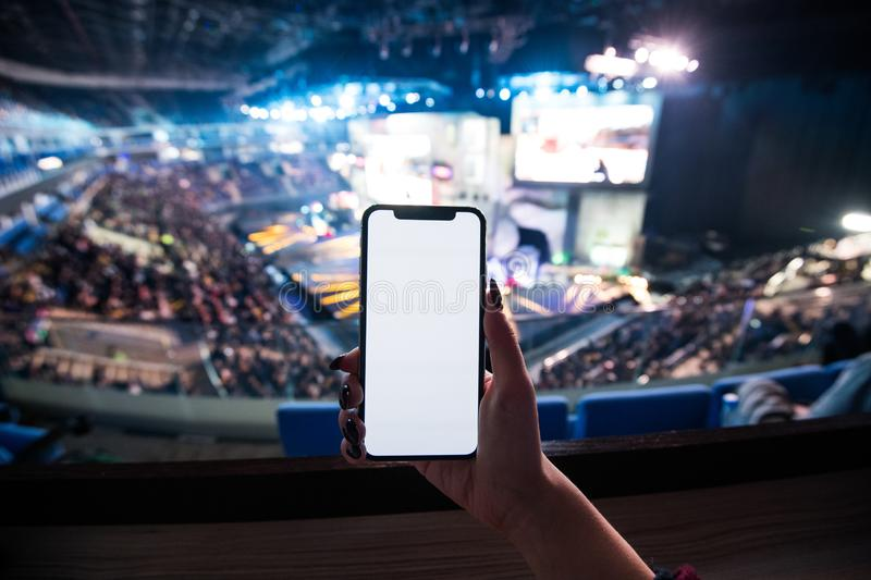 Woman`s hands using digital application on the mobile smart phone at esport event at big arena. Copy space. Woman`s hands using digital application on the stock image