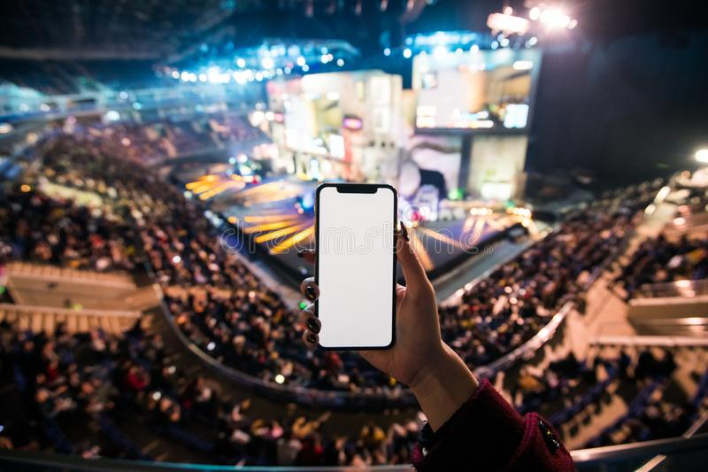 Woman`s hands using digital application on the mobile smart phone at esport event at big arena. Copy space. Woman`s hands using digital application on the stock images