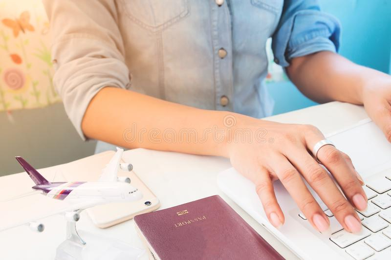 Woman`s hands using laptop computer, Airplane model and passport royalty free stock images