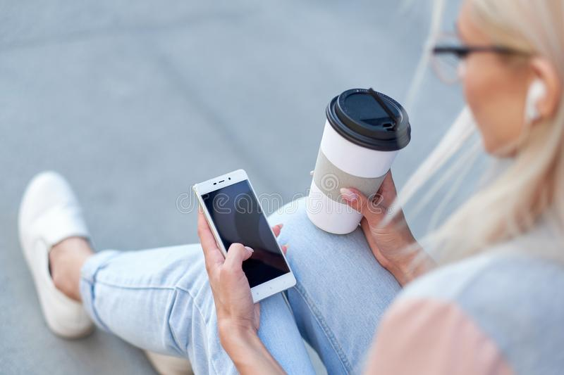 Woman`s hands using phone and holding paper cup with coffee. Teen hipster online internet consept.  royalty free stock photography