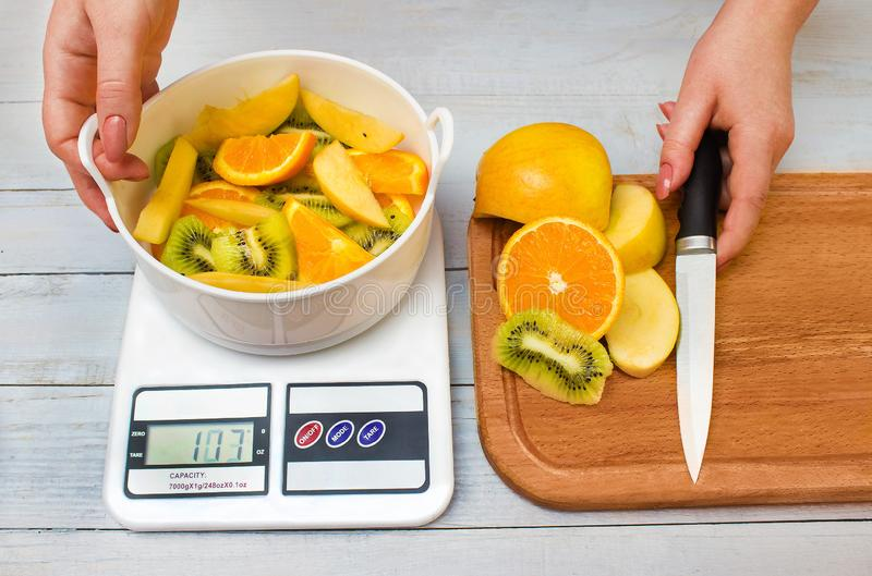 Woman`s hands weighing sliced fruits stock images