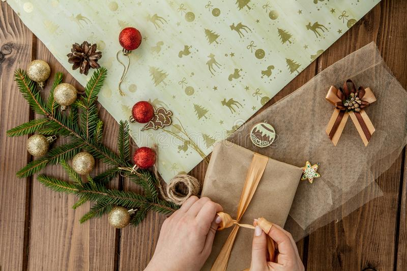 Woman s hands wrapping Christmas gift, close up. Unprepared christmas presents on wooden background with decor elements and items royalty free stock image
