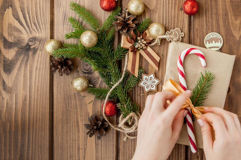 Woman s hands wrapping Christmas gift, close up. Unprepared christmas presents on wooden background with decor elements and items royalty free stock photo