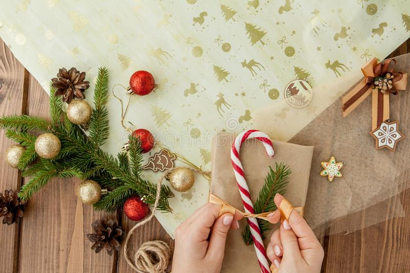 Woman s hands wrapping Christmas gift, close up. Unprepared christmas presents on wooden background with decor elements and items royalty free stock photos