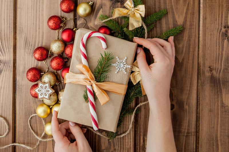 Woman s hands wrapping Christmas gift, close up. Unprepared christmas presents on wooden background with decor elements and items stock images