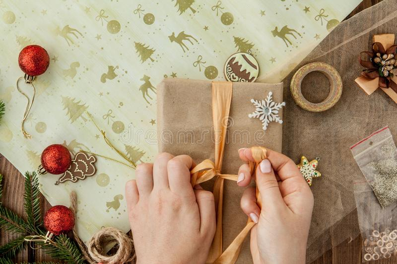 Woman s hands wrapping Christmas gift, close up. Unprepared christmas presents on wooden background with decor elements and items royalty free stock images
