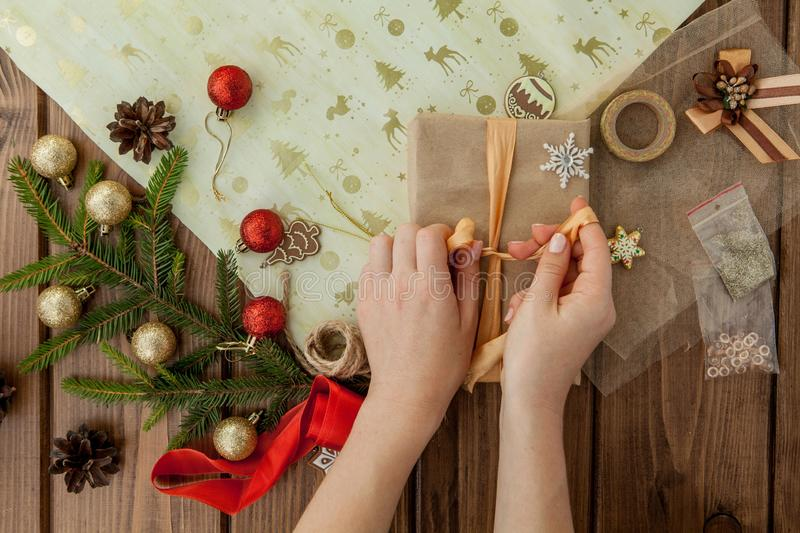 Woman s hands wrapping Christmas gift, close up. Unprepared christmas presents on wooden background with decor elements and items stock image