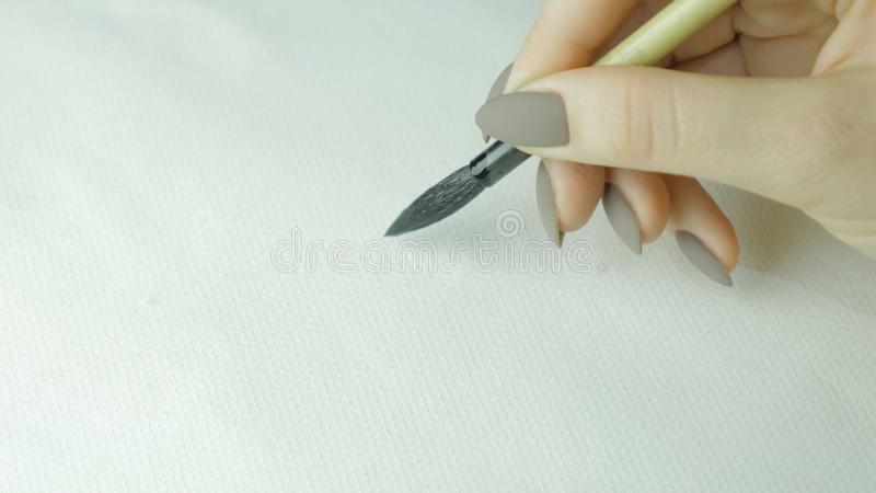 Woman`s hands writing Chinese hieroglyph. Female hand holding a writing brush calligraphy Chinese characters, close up stock photos