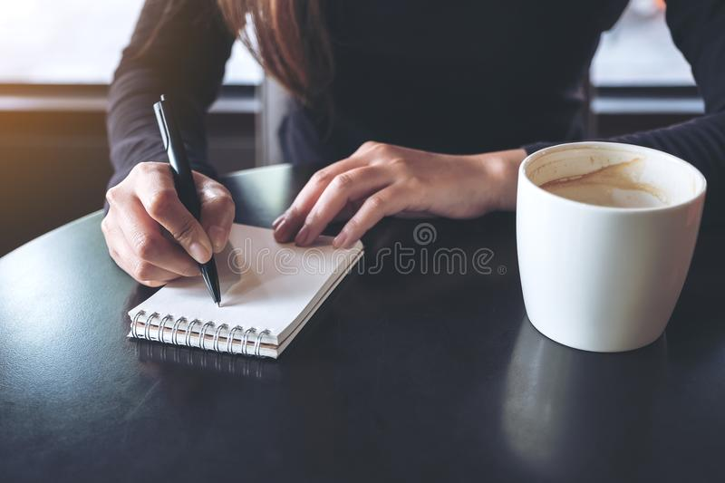 A woman`s hands writing down on a white blank notebook with coffee cup on table. Closeup image of a woman`s hands writing down on a white blank notebook with stock images