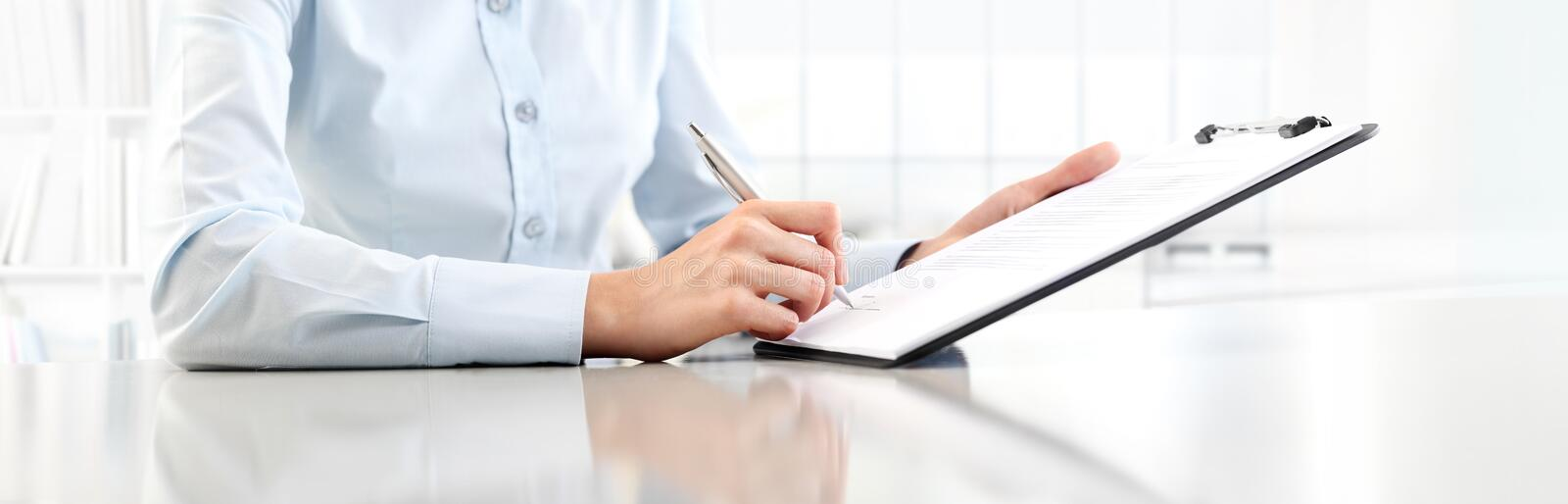 Woman`s hands writing on sheet in a clipboard with a pen, isola royalty free stock photos