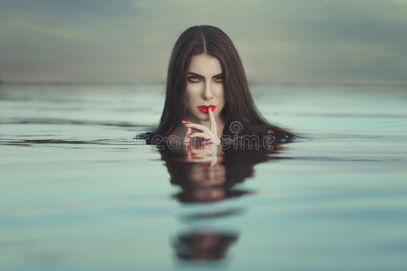 Woman`s head sticking out of the water. Woman`s head sticking out of the water, put a finger to his lips royalty free stock photography