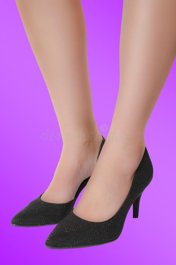 Woman`s legs with black high-heeled shoes stock photos