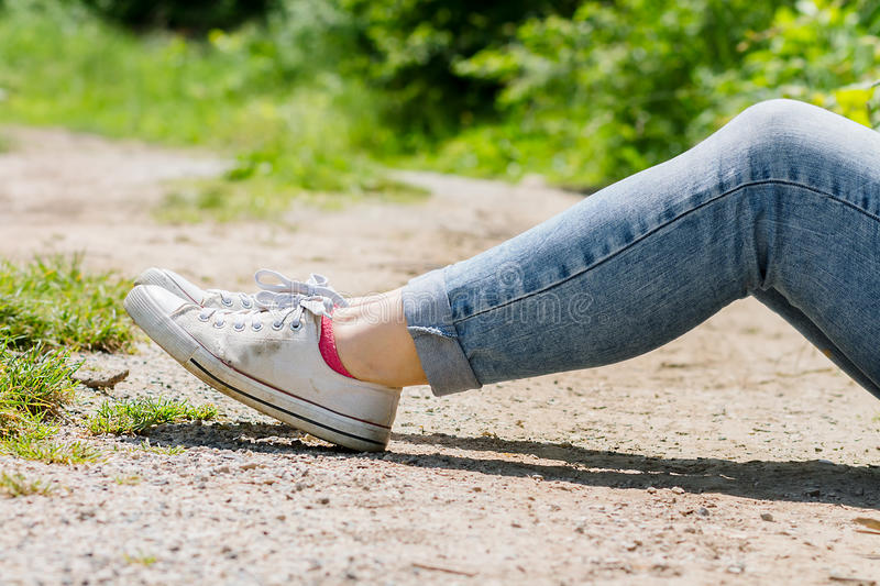 Woman`s legs in blue jeans and white canvas sneakers royalty free stock images