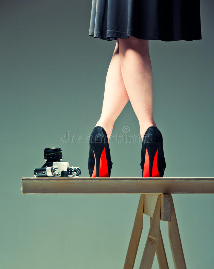 Woman's legs and the camera royalty free stock photography