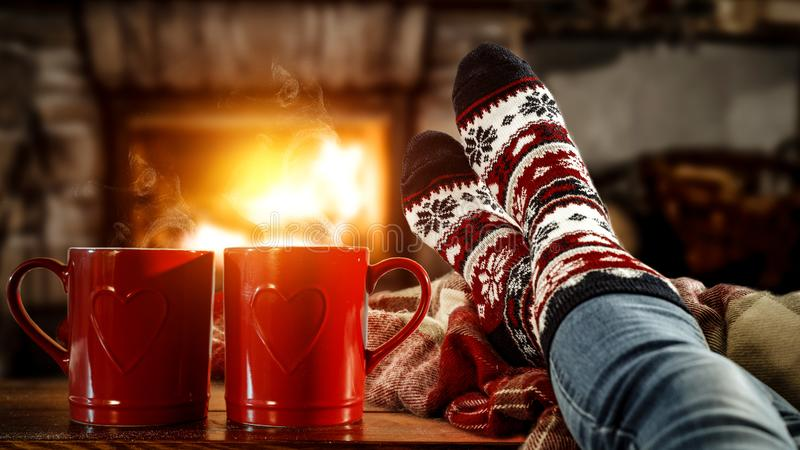 Woman`s legs with christmas socks and red mugs of coffee or tea and home interior with fireplace and dark wall background. stock photos