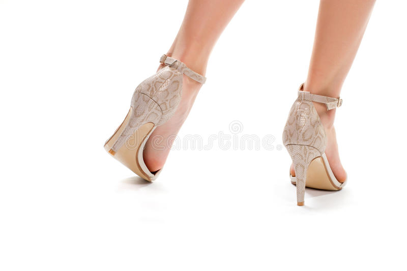 Woman's legs in heel shoes. Beige heels with straps. Girl's footwear on white background. Exclusive designer shoes royalty free stock images