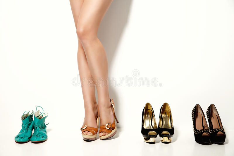 Woman's legs and many shoes over white background. This image has attached release stock image