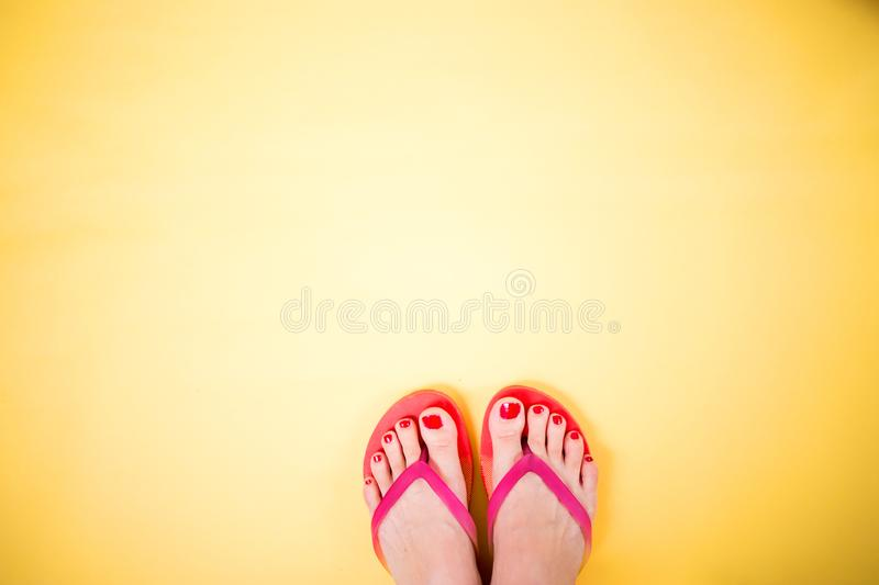 Woman`s legs wearing pink flip flops on yellow background with copy space. Woman`s legs with red pedicure wearing pink flip flops on yellow background with copy royalty free stock photography