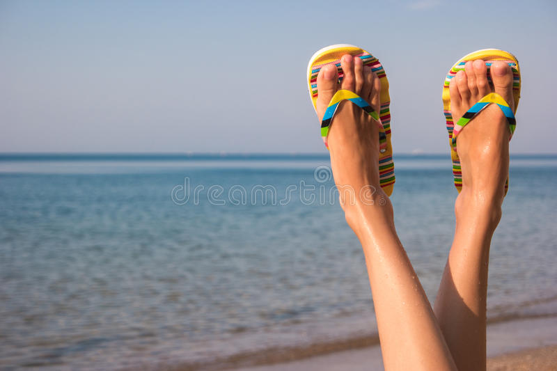 Woman`s legs and sea. Feet wearing flip flops. Leave bustle and problems behind. The dream vacation stock photography