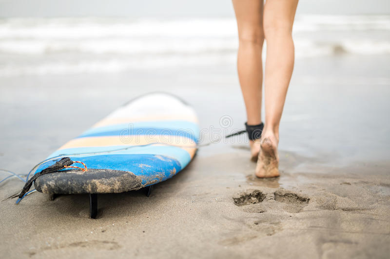Woman`s legs and surfboard stock images