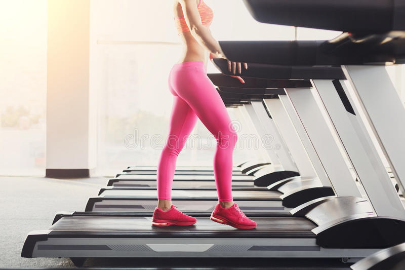 Woman`s legs on treadmill in fitness club, healthy lifestyle. Side view of attractive young unrecognizable woman in pink leggings running on treadmill in gym stock images