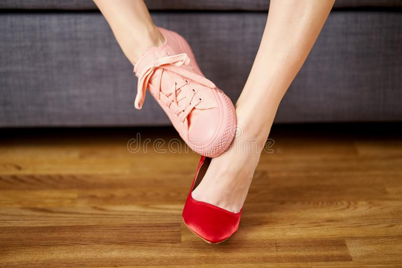 Woman`s legs in two different shoes with red high heels and coral sneakers on gray couch background. stock images