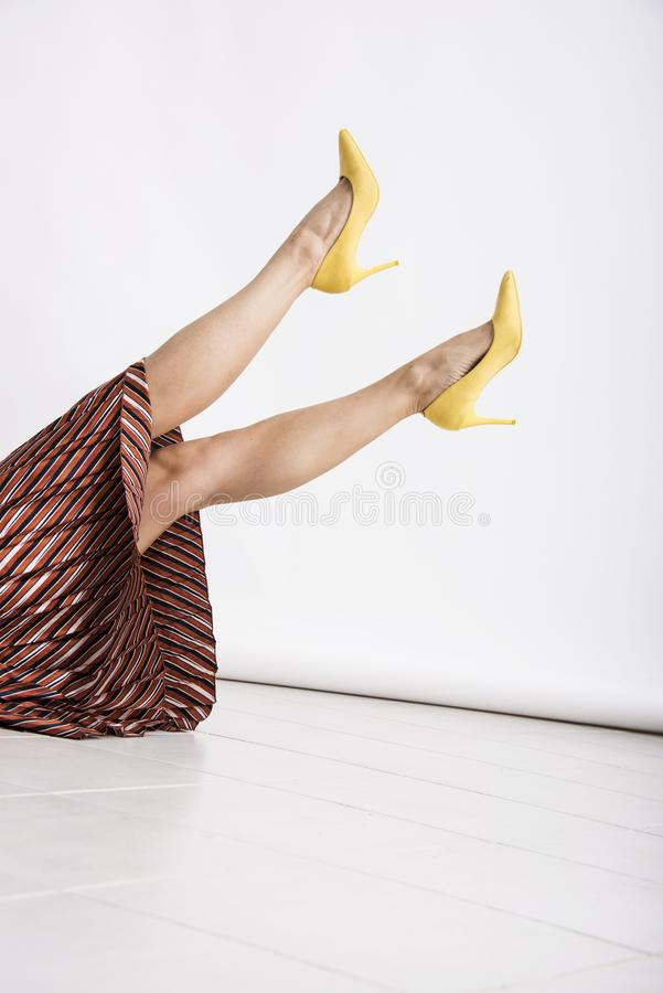 Woman`s legs up in the air with yellow high heeled shoes. royalty free stock photos