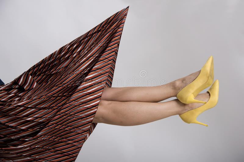 Woman`s legs up in the air with yellow high heeled shoes. Beauty and fashion abstract conception royalty free stock photos