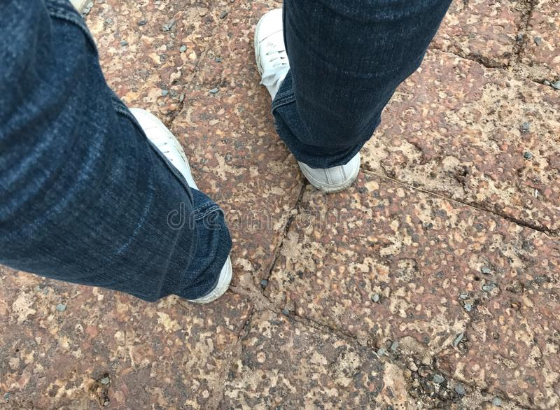 Woman`s legs wear navy blue jeans and white sneakers standing on antique brown brick street royalty free stock image
