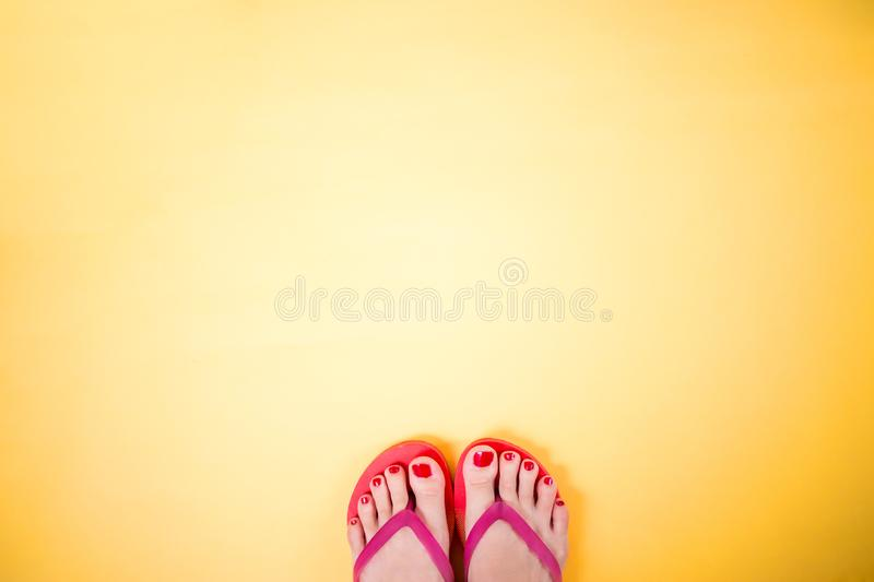 Woman`s legs wearing pink flip flops on yellow background with copy space stock photography