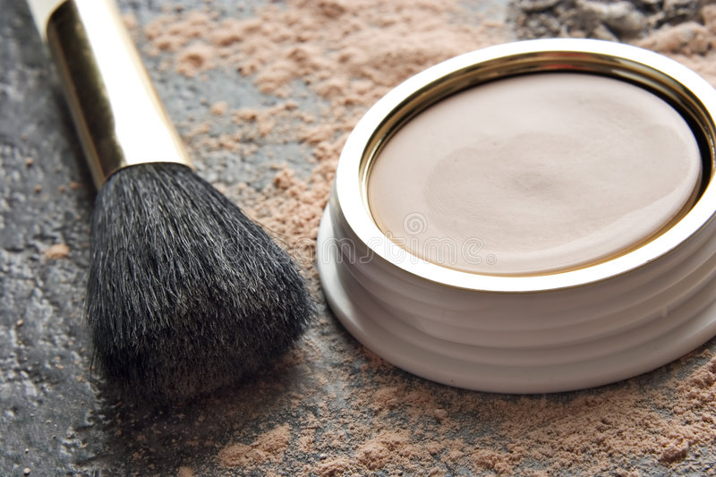 Woman's makeup. Powder makeup and applicator brush placed on a granite tabletop royalty free stock images