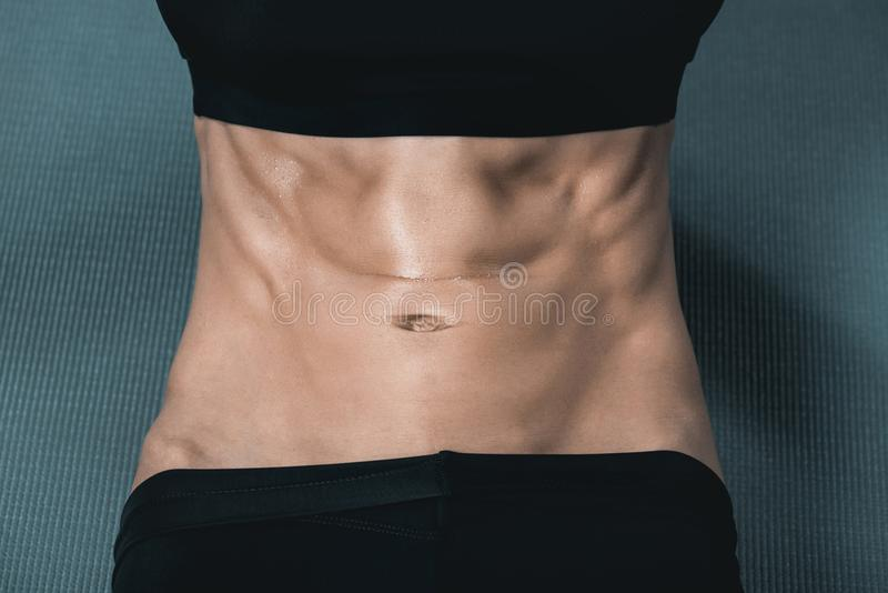 woman's muscular body with abs on mat royalty free stock photos
