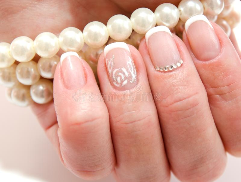 Woman`s nails with beautiful french manicure fashion design with stock images
