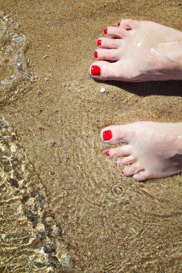 Woman`s pedicured feet with red nail polish on toes in the sand in water. stock photo