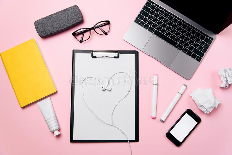 Woman`s pink office desk with headphones laid out like a heart. Woman`s workplace with laptop, smart phone with blank stock photo