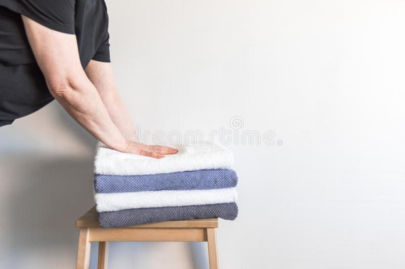 Woman`s placing stacks of different towels onto the wooden chair. Family and home concept. Woman`s placing stacks of different towels onto the wooden chair royalty free stock photos