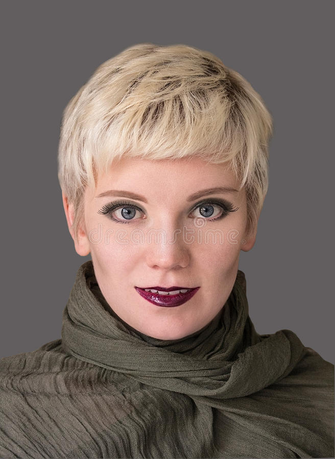 Woman`s portrait blonde. Fashion hairstyle, make-up in grey shades. Beautiful woman with short hair blonde wearing khaki scarf on grey background. Close-up royalty free stock images