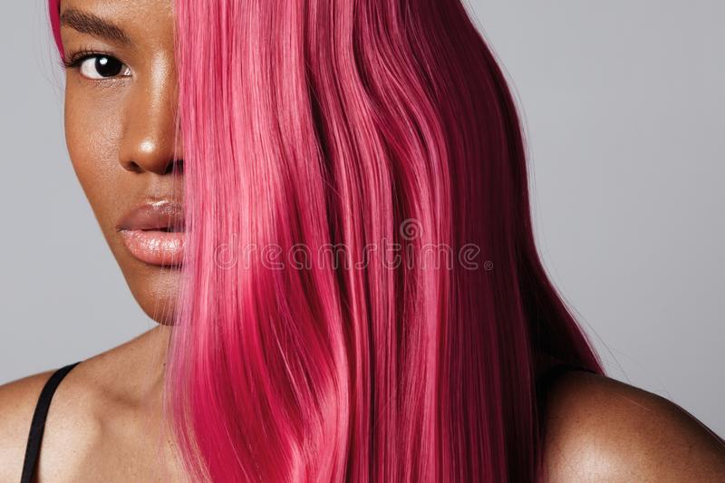 Woman`s portrait with a half of a face covered by pink hair stock images