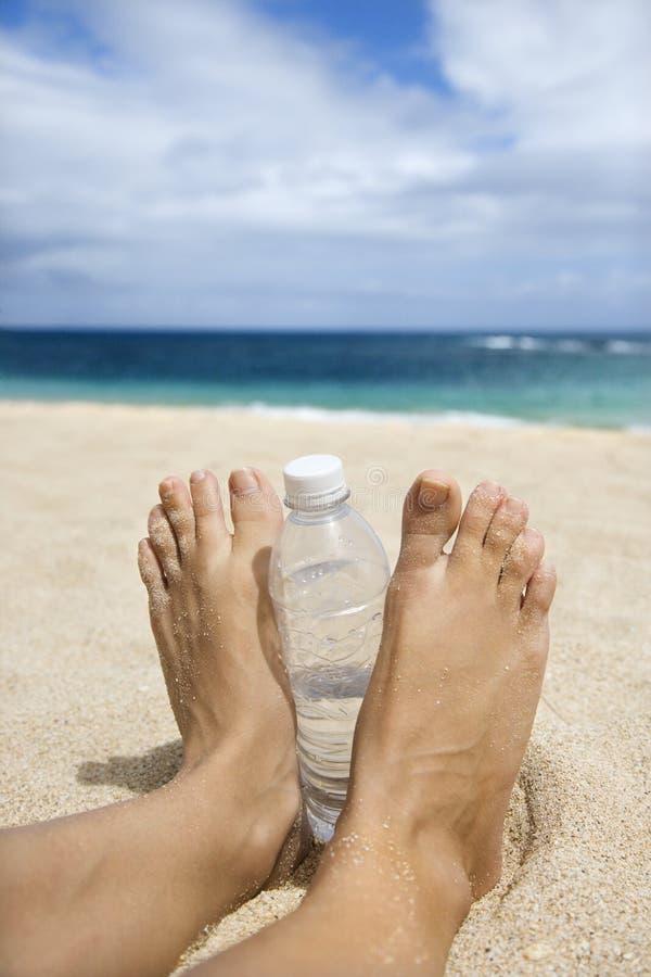 Woman's sandy feet on beach. stock photos