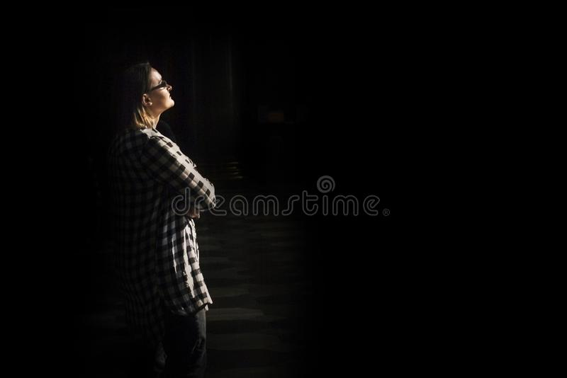 Woman`s silhouette under light on black background royalty free stock photography