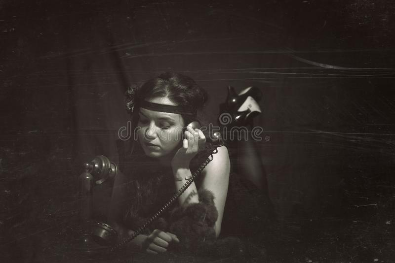 Woman 1920s style belly downwith old phone. Vintage style photography with reconstructed artifacts. royalty free stock photography