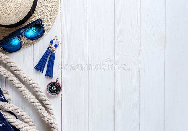 Woman`s summer hat, shell, wheels on white wooden background, flat lay, top view. Travelling essentials. stock images