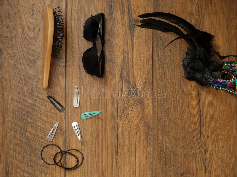 Woman`s wooden brush, elastic bands, Black sunglasses, masquerade mask and metal clips for hair on a wooden table surface, Copy royalty free stock photography