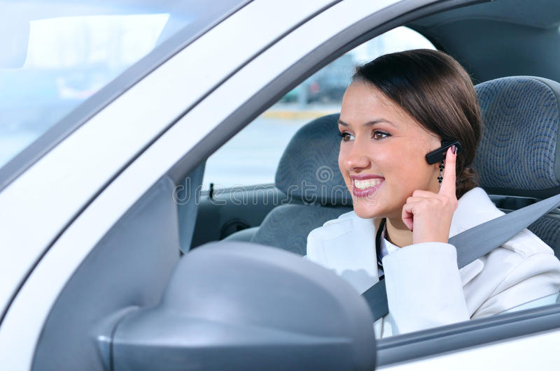 Woman is safely talking phone in a car royalty free stock photography