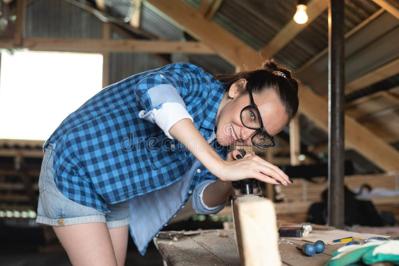 Woman in safety glasses working planer on wooden Board front view stock image
