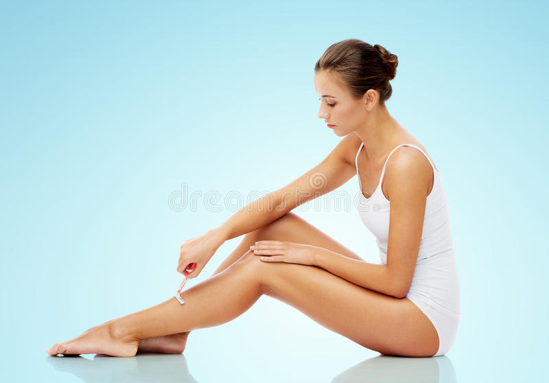 Woman with safety razor shaving legs over blue stock photo